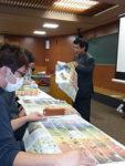 北海道新聞の見開き広告面を大学生たちに配り、模擬授業を進める山崎さん(右)