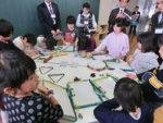 公開授業で楽器に触れながら、取材メモを書く資生館小の児童