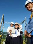 高さ10メートルの足場の上で新幹線の取材をする新聞部の中野部長(中央)ら3人と山崎所長(右)