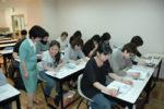 清藤講師(左)の指導で記事を朗読、内容を要約する「こども学舎」の学生