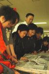 玄関に設けた新聞コーナーに立ち寄る児童。実践開始にあたり、山田教諭(中央)がいち早く整備した