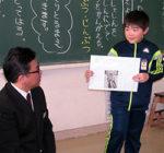 ワークシートを手にした子どもに発表の基本を指導する大武教諭(左)