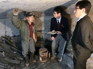 炭焼き窯は落田さん(左)の手作り。熱心に話に聞き入る豊岡さん(中央)と小山教諭