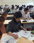 記事とコメントをまとめたA4判の作品を回し読みする教員たち