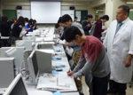 手書き新聞を審査する月寒高定時制の2年生たち。右端は青島正樹教諭
