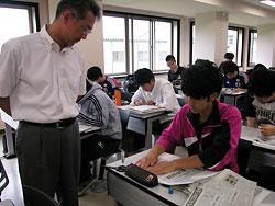 NIE講座で、学生の新聞スクラップ作りを指導する福沢さん