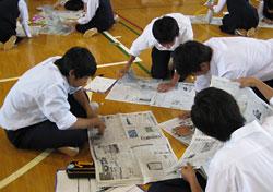 「切り抜き集会」で、新聞の中からお目当ての記事を探す1年生=函館稜北高校提供