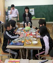 給食指導で和寒の「越冬キャベツ」を子どもたちに示す佐藤教諭(中央)。左は加藤教諭