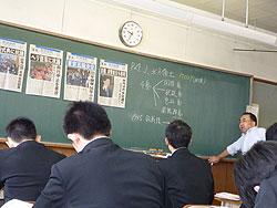 琉球新報の号外を黒板に張り、時事問題研究の授業をする毛利教諭(右)