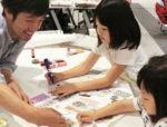 世代を超えてだれもが楽しめる「まわしよみ新聞」。小さな子供も夢中になる=7月、札幌の体験会