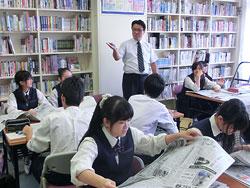 高橋教諭(中央奥)の指導で、新聞をめくって理不尽な事例を探す生徒たち