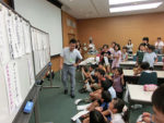 自分たちが考えた見出しを見ながら話し合う静岡市立城北小5年生と漆畑浩明教諭(左)