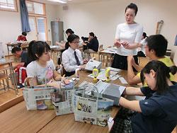 地元のニュースなどを前面に出したエコバッグ(手前)と狩野千賀子教諭の指導で製作に励む生徒たち=18日