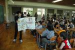 「レッツえいご!」の英文記事を見せる平野教諭
