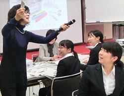 切った記事は「チャリーン」と言いながら箱に入れるのがルール。渡辺さん(左)のかけ声で参加者は「チャリーン」を練習