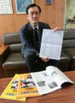 「札幌市小学校NIE計画表」の原案を手にする上村副会長。手前の報告書に収められた実践との関連を示すことも検討している