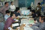 休日にも集合し、効果的な新聞活用法を検討する藤本講師(奥左の座っている人)と実践教諭ら