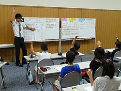 プロ野球の勝敗表を使い割合を求める数式の復習をする斉藤雅彦教諭と音更小の児童たち
