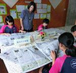 玉名中のNIEコーナーで生徒の新聞閲覧を見守る坂口教諭