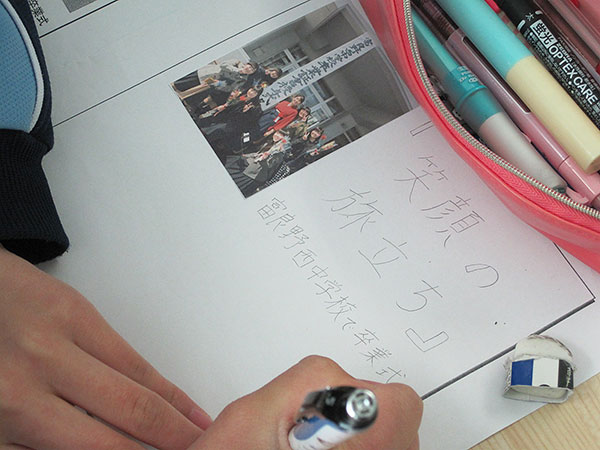 「卒業式新聞」作成の様子。写真と見出しの構図が決まり、記事を書き出しています