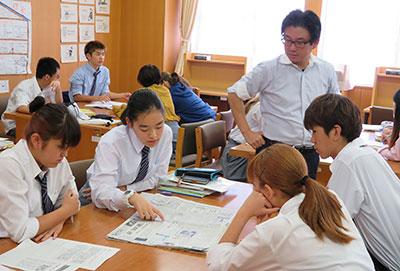 現代社会の授業で、新聞6紙を読む都立国際高校の生徒と、担当教諭の宮崎さん=11日