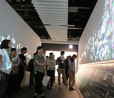 新聞を支えた技術を博物館内の情報のタイムトンネルを通りながら見学する教員たち