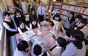 ニュース検定に向け図書館で新聞を読み比べる生徒たち。後列中央が北川孝博教諭、左隣が新田裕子司書