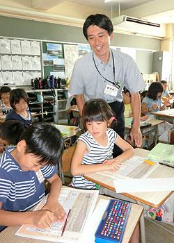 ワークシートを使って俳句を学習する児童の様子を見つめる菊池健一教諭=16日、海老沼小