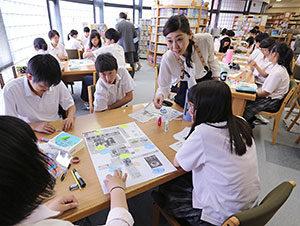 壁新聞を仕上げる生徒たちに助言する梅津麻紀教諭=12日、札幌創成高