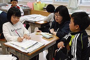 インタビューする子どもにアドバイスする板谷令子教諭(右から2人目)=6月8日、泊小