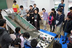 模型を使った土石流の実験。「砂防ダムなどがあれば、被害は少なくできる」と説明する笠井准教授(中央)