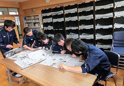 昼休みの図書室。生徒たちは棚から新聞を取り出し読み合っていた=20日