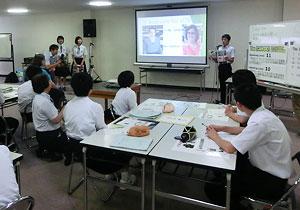 英字新聞をスクリーンに映して発表する由利本荘市立由利中の3年生