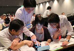 NIE秋田大会で教育向け電子新聞の活用を体験してもらう二田貴広教諭(中央左から2人目)=秋田県民会館ジョイナス