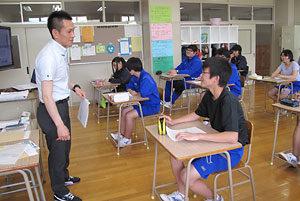 新聞記事を使って授業を進める山田耕平教諭と3年生の生徒たち