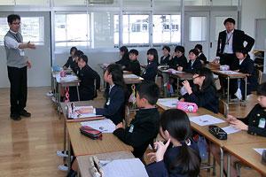 広島カープに復帰した黒田博樹投手の記事を使い、4年生のNIE授業を進める宮里洋司教諭(左)。右側は担任の岩本浩司教諭