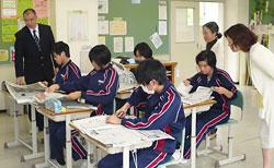 記事を選んで切り抜く中学3年生と平沼教諭(左)