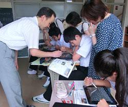江村教諭(左)の指導で、記事データベースを検索する福山市立山野中の3年生