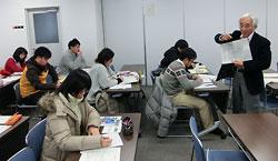 北海道新聞と読売新聞の社説のコピーを示しながら授業を進める北川保さん=11日、三重大