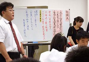 日豪EPAに関する北海道新聞の社説(社説A)の論点を書き出しながら授業を進める腰山潤教諭(左端)