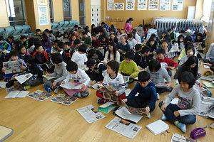 北海道新聞の出前講座で配られた新聞を見る屯田北小の5年生たち