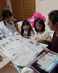 家族4人で新聞を読む鎌田さん一家。父慎一さん(左)と母幸子さん(右)も加わり大事な夜のひとときだ