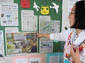 新聞記事を掲示する愛宕東小の三谷智恵子さん