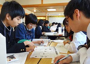 自分たちが作った高校新聞を見ながら18歳選挙権について議論する生徒たち=6日、士別市民文化センター