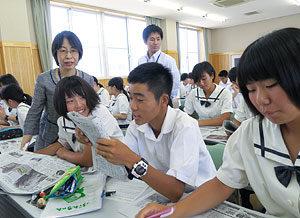 「へぇ!」の記事を報告し合う生徒たち。後方左側が畝岡睦実教諭=9日、岡山南高