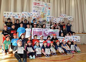 「チャレンジマラソン」のゴール後、取り寄せた新聞などを手に記念撮影する小中学生=4日、上浦幌中央小学校