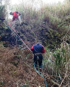 2500年前にできた直径30メートル、深さ25メートルの火口にザイルで下りる生徒=3月14日、雄山の標高390メートル地点(川澄隆明教諭提供)