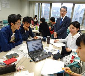 浅川教授の助言を受け、壁新聞作りに取り組む北大の学生ら=6月13日
