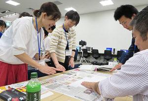 各新聞の記事などを切り貼りして、まわしよみ新聞を製作する参加者たち=6月24日
