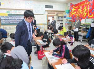 NIEの授業を受ける安平町立早来小の6年生と担任の冨樫忠浩さん